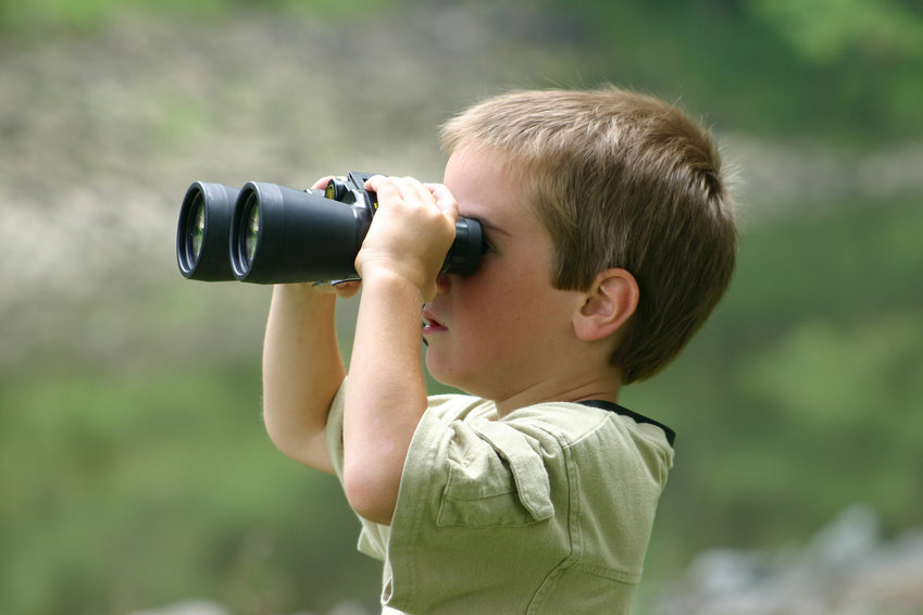 boy looking through binoculars